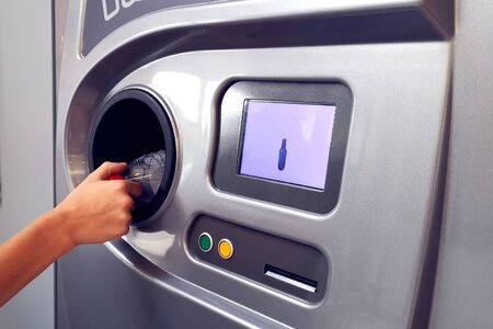Man returns bottles and cans of reusable packagings in reverse vending machine. Environmental protection concept