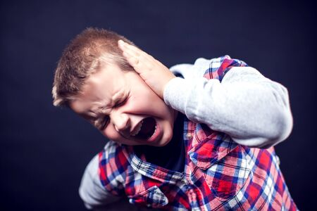 A boy feels strong ear pain. Children, healthcare and medicine concept Banque d'images - 131702182