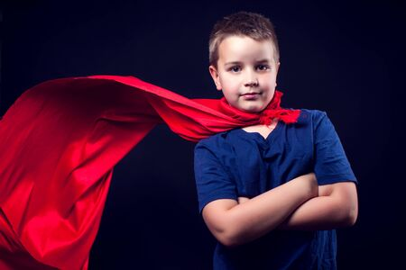 A cute boy with red cloak like a superhero. Children and success concept