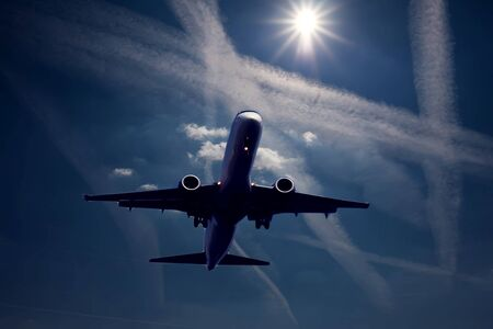 Plane in the blue sky with chem trails. Environmental pollution concept