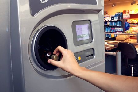 Man returns bottles and cans of reusable packagings in reverse vending machine. Environmental protection concept Reklamní fotografie