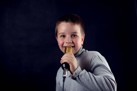 A portrait of a boy with microphone in front of dark background. Children, talent and entertainment concept Imagens