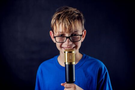 A portrait of a teen boy with eyeglasses holds microphone in front of dark background. Children, talent and entertainment concept