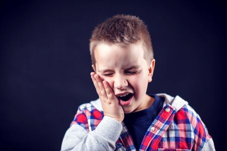 A boy feels strong tooth ache. Children, healthcare and medicine concept Banque d'images - 131702400