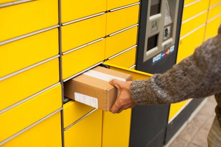 Yellow self-service post terminal machine. Man recieve a parcel Archivio Fotografico