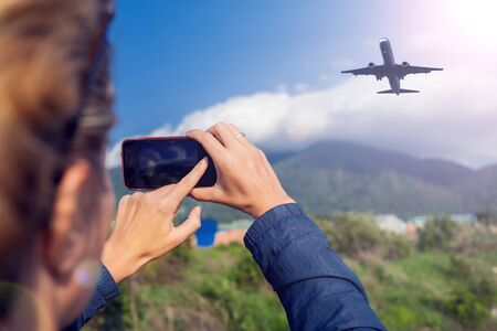 Woman makes photo of plane in the sky over mountains. Holiday and travel concept