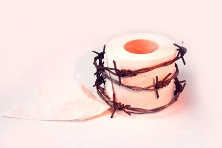 Toilet paper with barbed wire around it on white background. People, healthcare and medicine concept.