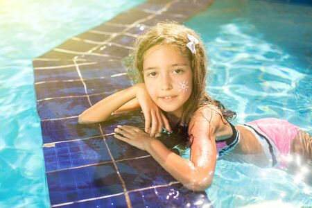 Kid girl with sun protection cream on her skin spends time in the pool. Children, summer, holiday and healthcare concept