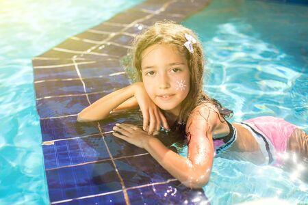 Kid meisje met zonnebrandcrème op haar huid brengt tijd door in het zwembad. Kinderen, zomer, vakantie en gezondheidszorgconcept Stockfoto