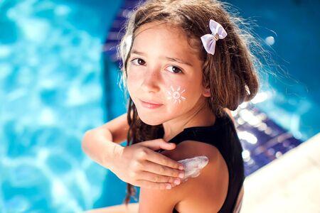 Kid girl applies sun protection cream on the skin. Children, summer and healthcare concept Archivio Fotografico