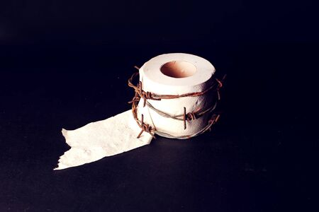 Toilet paper with barbed wire around it on black background. People, healthcare and medicine concept.