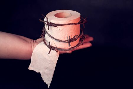 Woman holds toilet paper with barbed wire around it on black background. People, healthcare and medicine concept. Banco de Imagens