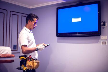 A man worker fix tv with blue screen