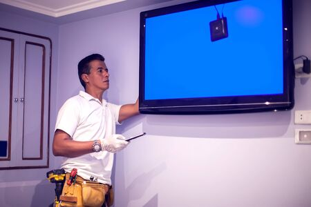 """A man worker fix tv with blue screen """"no signal""""."""