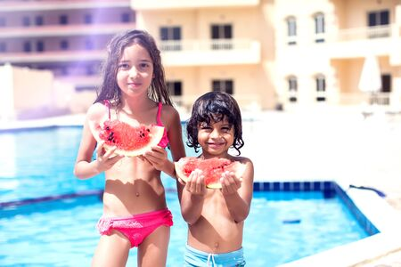 Little boy and girl eat watermelon at the swimming pool. Children and summer concept. Banque d'images - 131195787