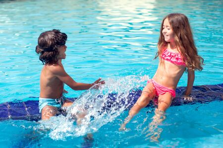 Niño y niña juegan en la piscina. Niños y concepto de verano. Foto de archivo