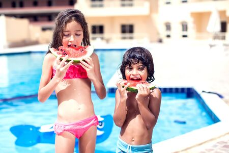 Little boy and girl eat watermelon at the swimming pool. Children and summer concept.