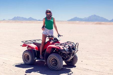 A group of quad bikes drive in the desert. Reklamní fotografie