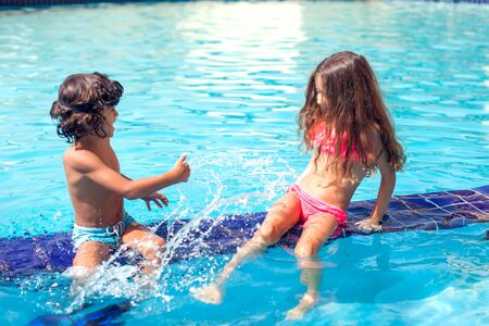 Little boy and girl play in the swimming pool. Children and summer concept. Standard-Bild