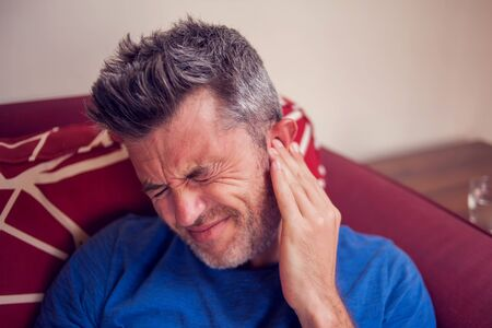 Man feels strong ear pain at home. People, healthcare and medicine concept Stock Photo