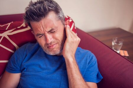 Man feels strong ear pain at home. People, healthcare and medicine concept