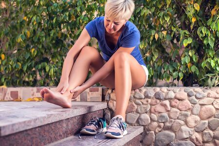 Woman feels foot pain while doing exercises. People, sport, healthcare and medicine concept