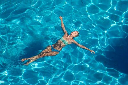 Woman swims in the pool outdoor. Up view. People, summer and holiday concept
