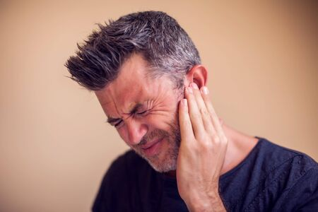 Man feels strong ear pain isolated. People, healthcare and medicine concept