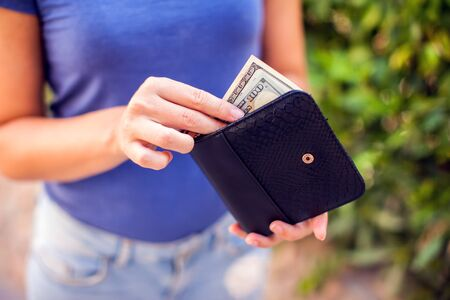 Woman holds an empty wallet in hands outdoor. Finance problem concept Фото со стока