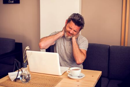 Man feeling neck pain while working with laptop. People, health care and technology concept