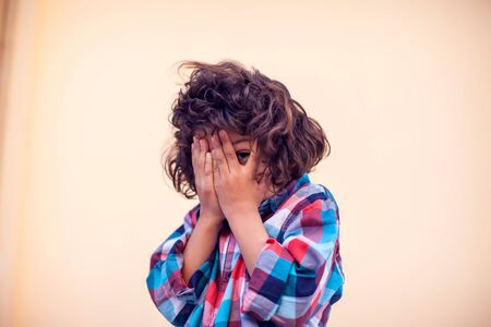 Closeup portrait of shy little kid with curly hair