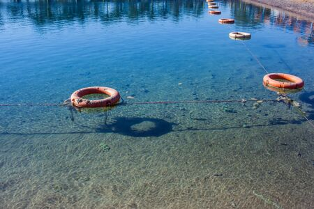 Protective buoys on sea surface. Fencing on water. Save zone for swimming Stockfoto