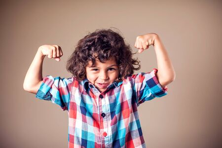 Portrait of a strong kid showing the muscles of his arms on grey background
