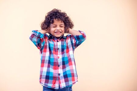 Little kid boy with curly hair closing ears with his hands in a protective position.
