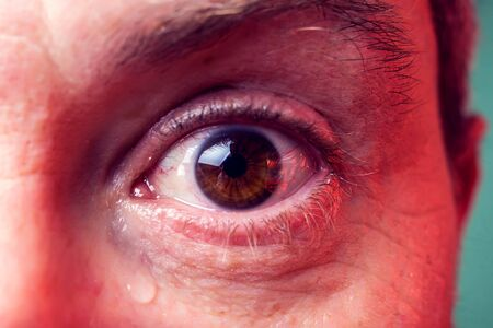 Close-up brown eye of a man with a tear. People, emotions concept
