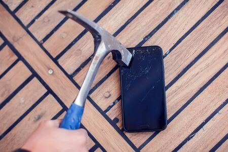 A man is breaking a smartphone lying on a wooden table with a hammer Фото со стока
