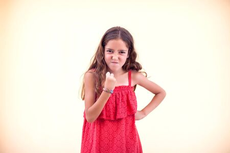 Little angry girl shows fist at camera. Children and emotions concept. Standard-Bild - 131275233