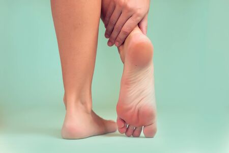 Woman feels strong foot pain. People, healthcare and medicine concept Imagens