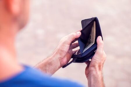 Man holds an empty wallet in hands outdoor. Finance problem concept Фото со стока