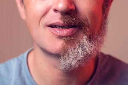 Un portrait d'homme avec demi-barbe et cheveux sur fond marron