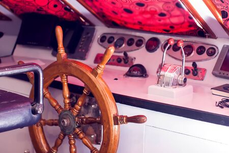 Wooden steering wheel and control panel on a yacht. Imagens