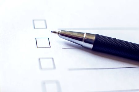 Checklist with a pen on white paper. Checkbox concept.