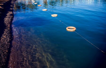 Protective buoys on sea surface. Fencing on water. Save zone for swimming