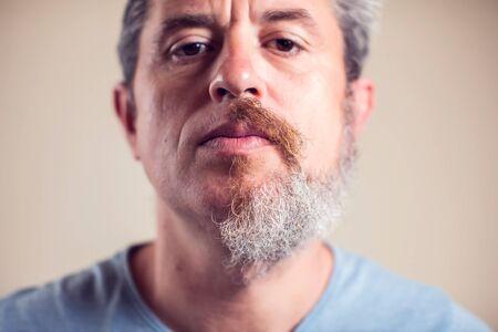 Ein Porträt eines Mannes mit Halbbart und Haaren auf braunem Hintergrund