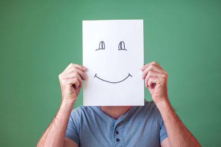 A portrait of man holding a card with smiling face. People, emotions and lifestyle Standard-Bild - 131280596