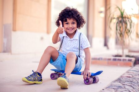 Little boy with curly hair with skateboard outdoor. Children and entertainment concept