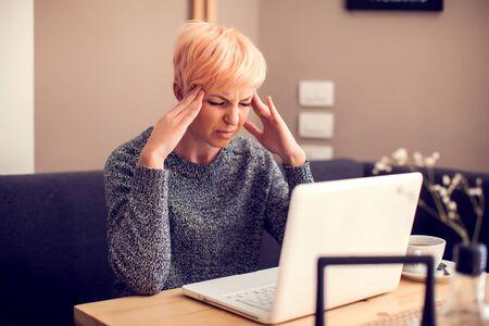 Gestresste Frau, die mit Laptop-Kopfschmerzen arbeitet. Menschen-, Gesundheits- und Technologiekonzept