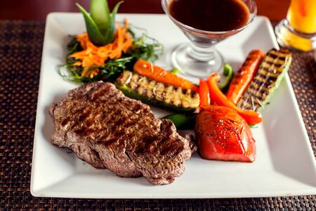 Beef steak with grilled vegetables served on white plate Stock fotó
