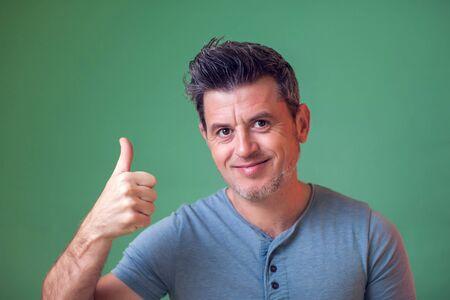親指を見せる笑顔の笑顔を持つ幸せな男。人と感情の概念。 写真素材