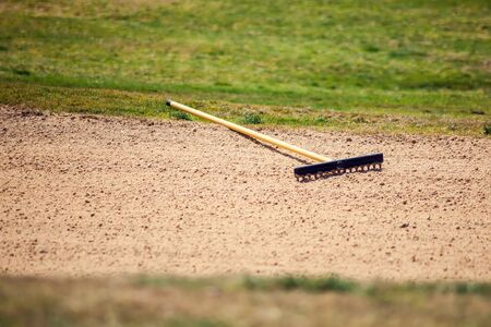 Sand rake equipment on the golf field. Sport and lifestyle concept
